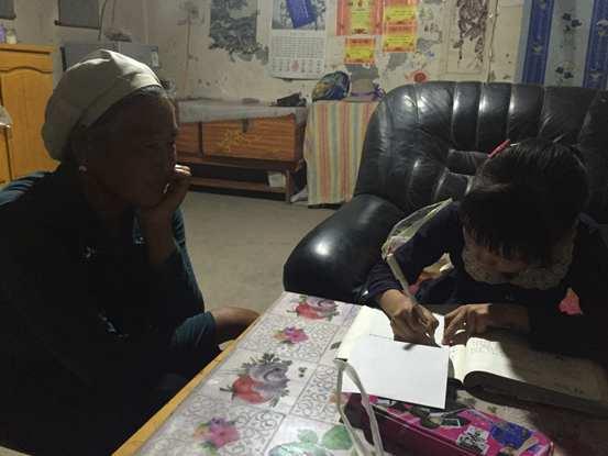 昏暗的灯光下,孩子仍在认真地学习
